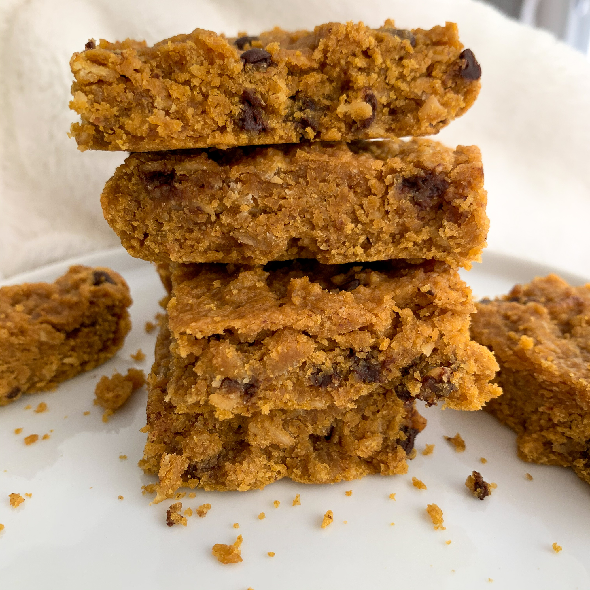 peanut butter and pumpkin chocolate chip oat bars on a white plate with a white background