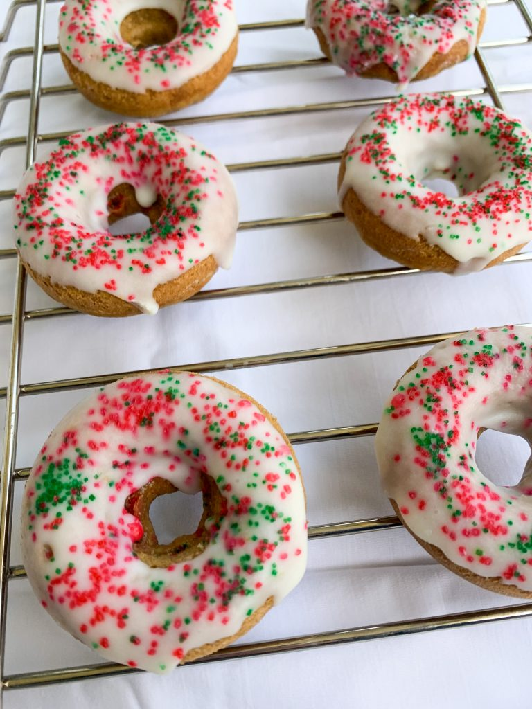 white chocolate holiday donuts on a cooling rack over a white sheet background