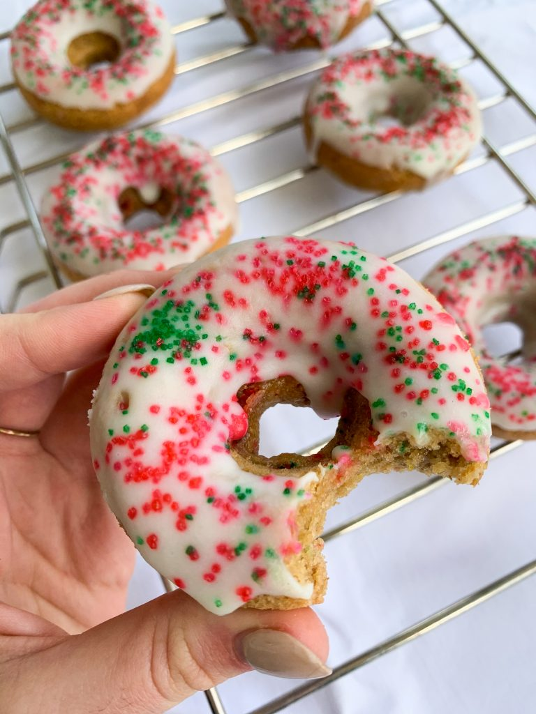 a hand holding one of the white chocolate holiday donuts over the rest of them