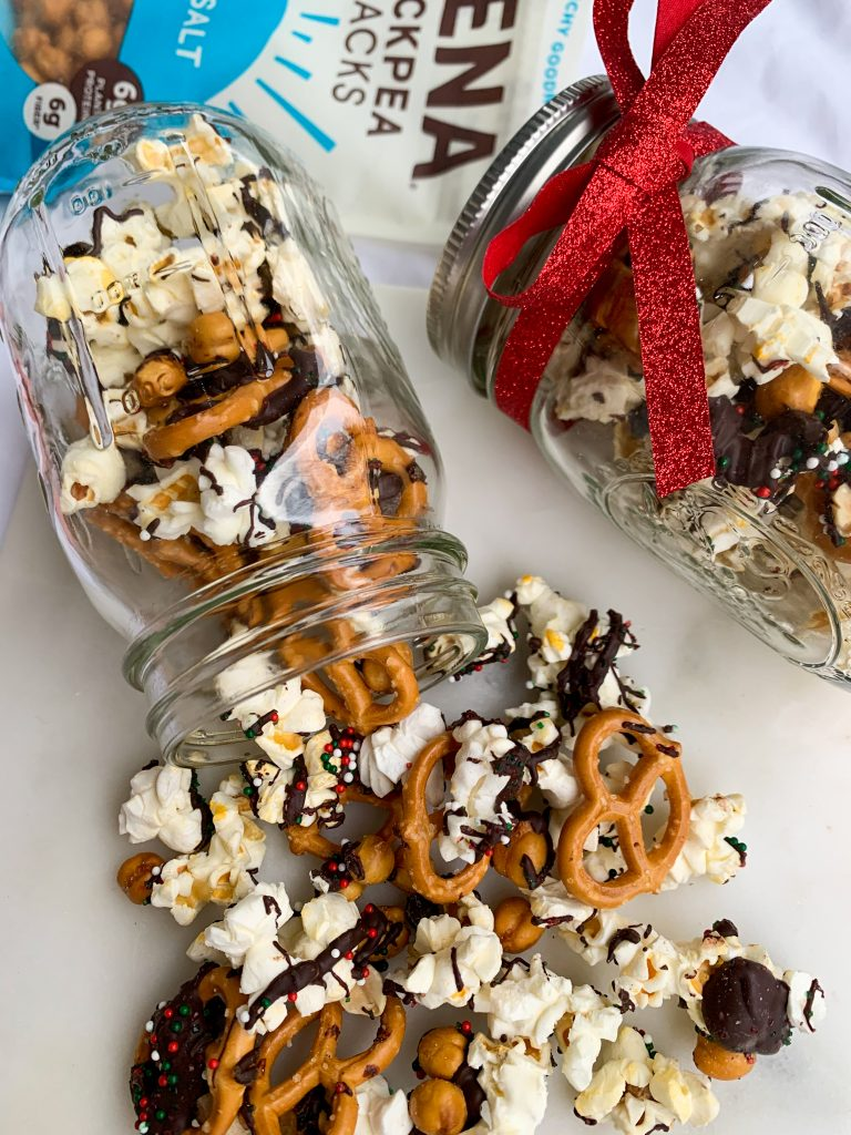 the sweet & salty christmas snack mix in two jars, spilling out of one onto a white board