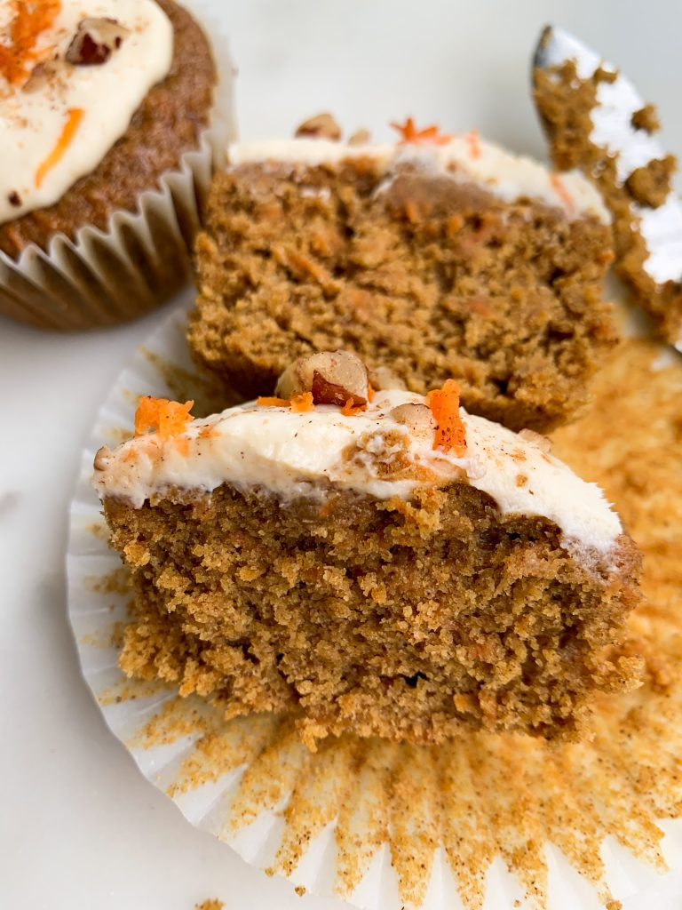 healthier carrot cake cupcakes on w a white board, one cut open, a knife on the side