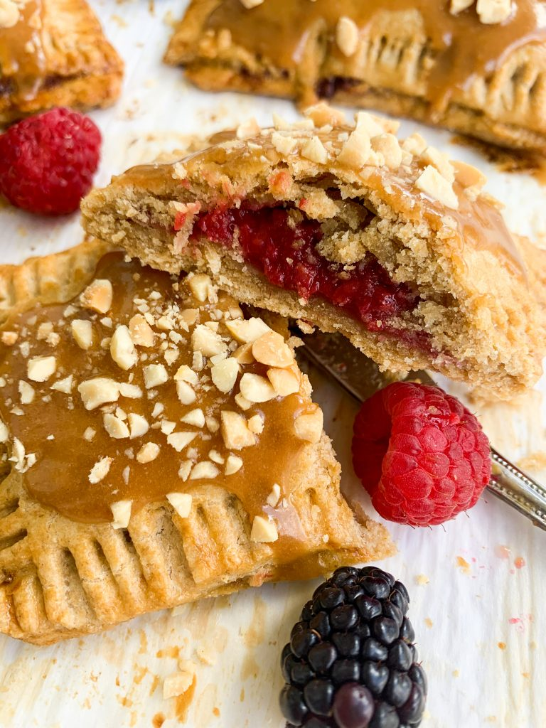 a homemade peanut butter and jelly pop tart cut open with a knife and some berries on the side