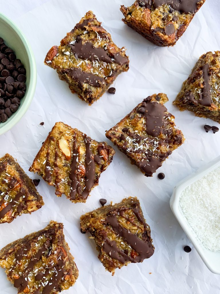 almond joy bars on a white surface, also a bowl of chocolate chips and a bowl of shredded coconut