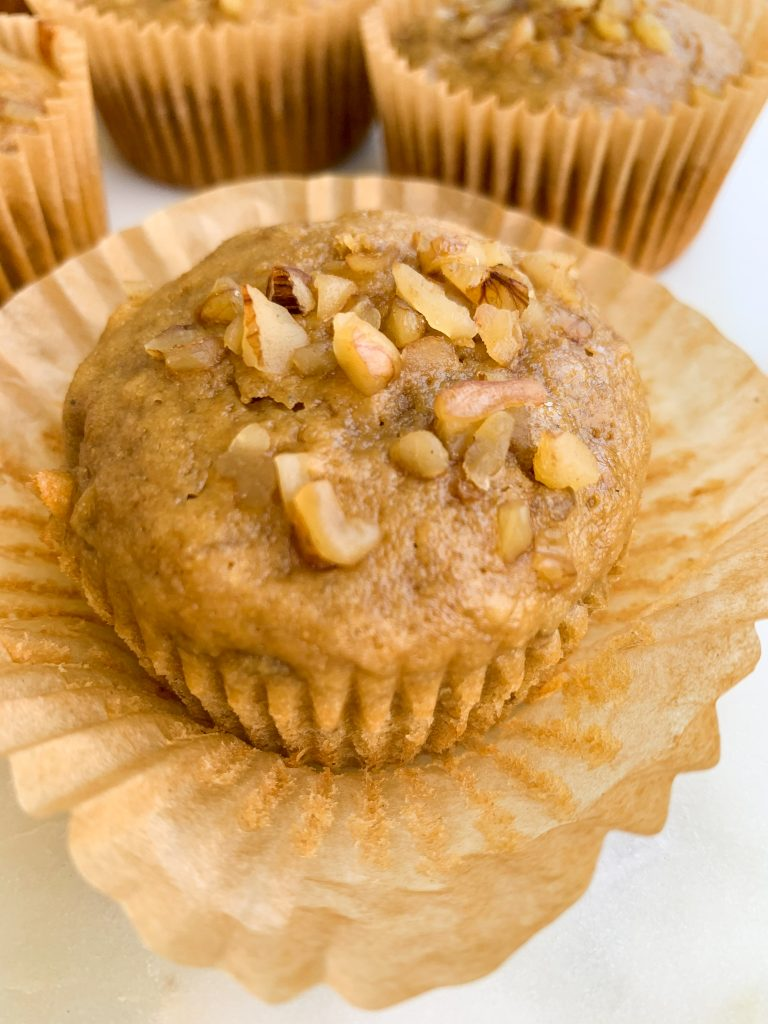 a close up of one whole wheat banana nut muffin on a white background