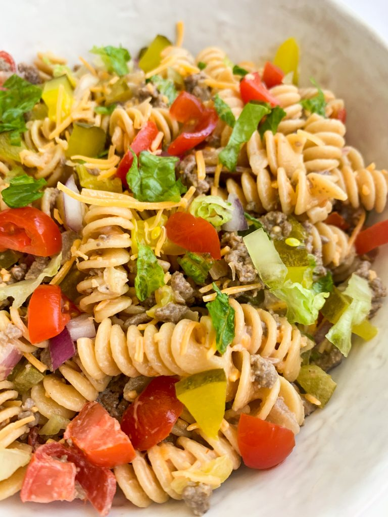a close up of the cheeseburger pasta salad all mixed together
