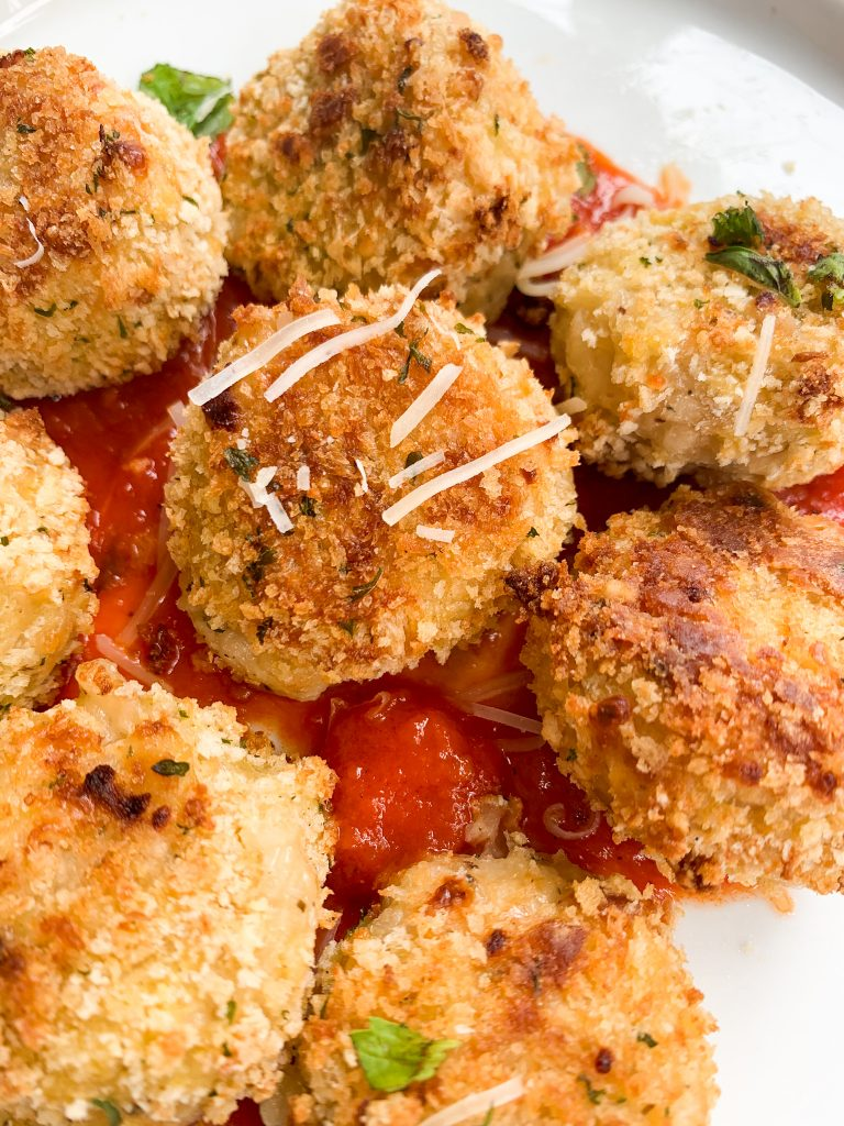 cheesy cauliflower rice balls over some marinara sauce