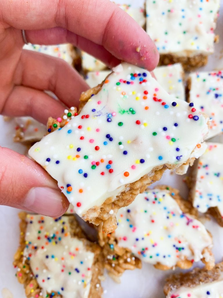 a hand holding one of the birthday cake cereal bars