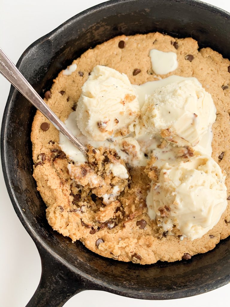 vegan chocolate chip cookie skillet with ice cream on top and a spoon