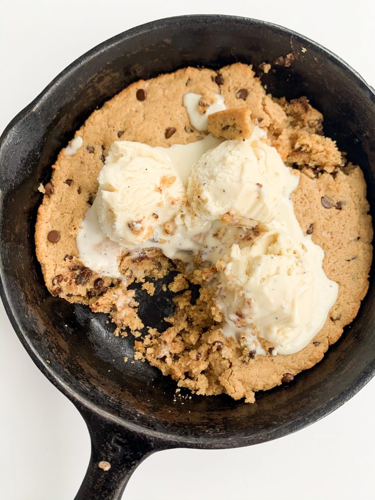 overview shot of chocolate chip cookie skillet, melted ice cream on top