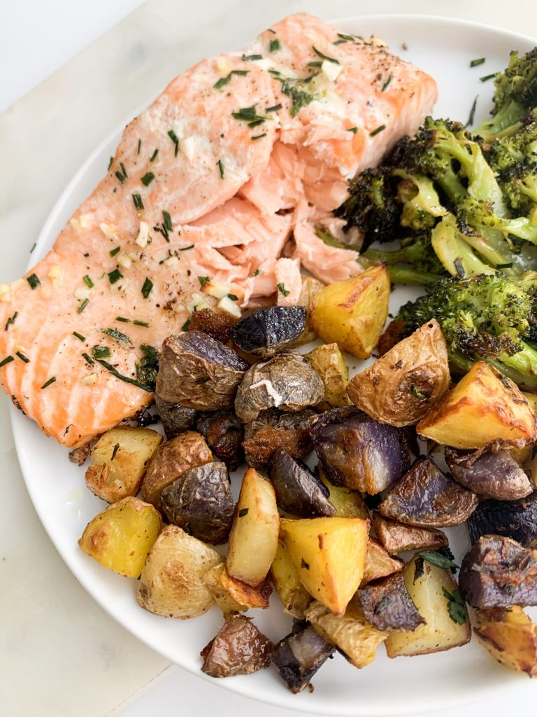 white plate with roasted colorful potatoes, broccoli, and salmon