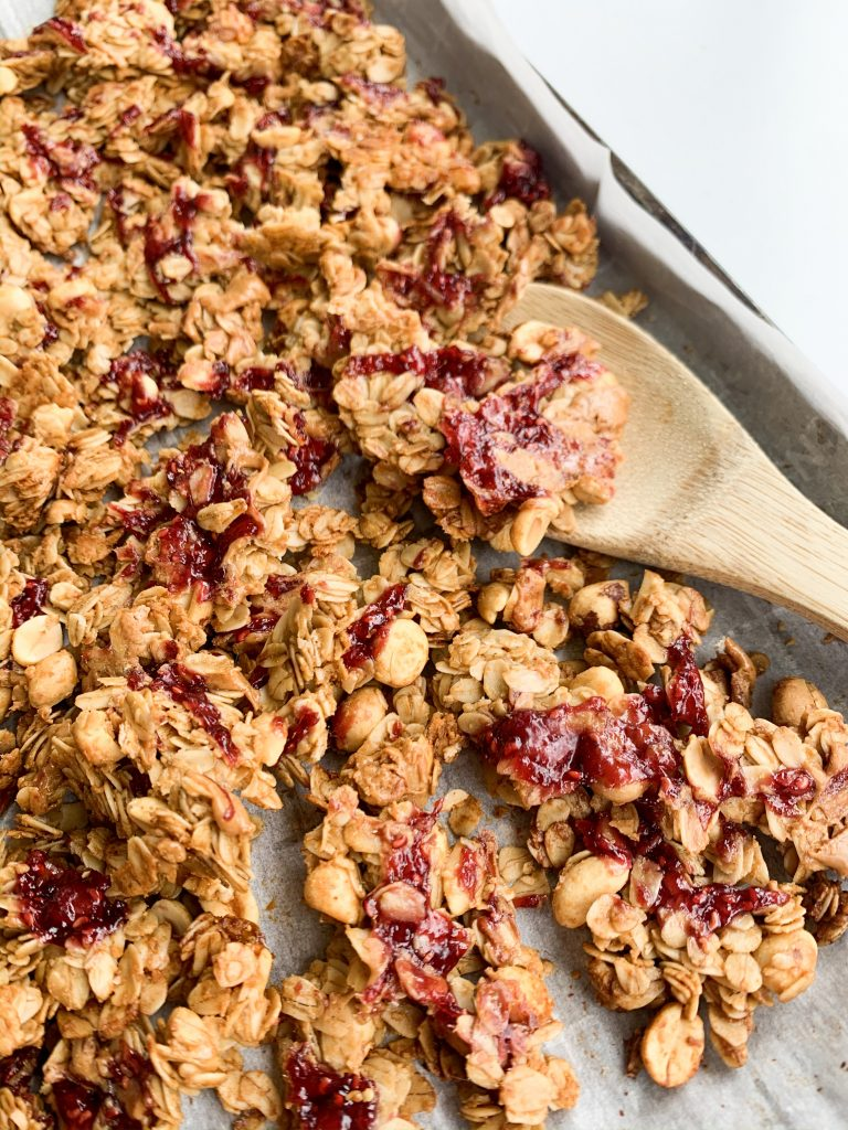 close up of a tray of granola with a wooden spoon scooping some up