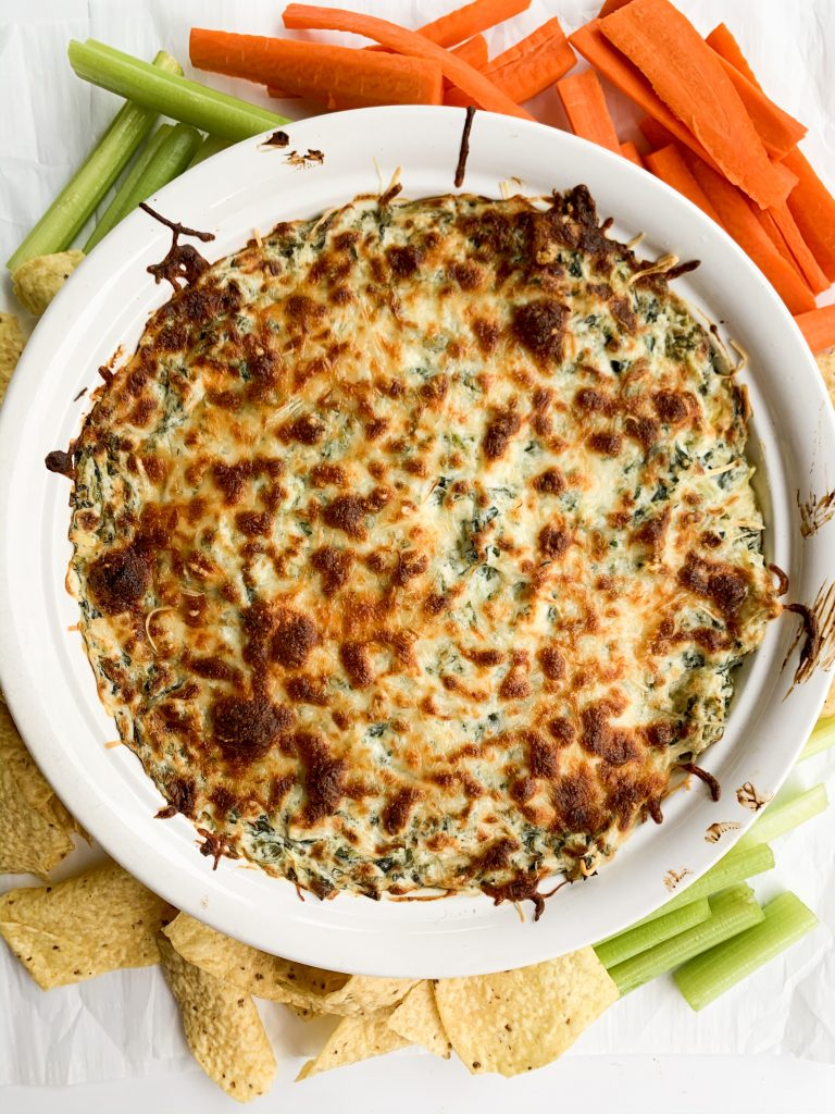 overhead shot of spinach dip in a round baking dish, surrounded by veggies and chips