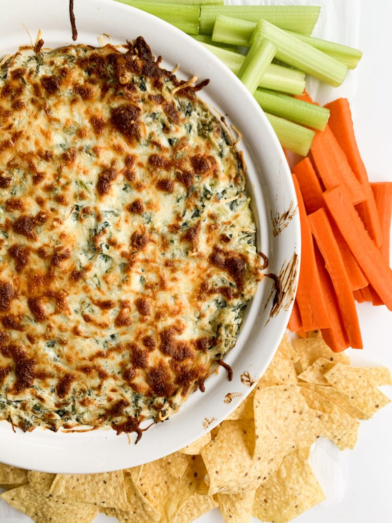 spinach and artichoke dip with carrots, celery, and chips on the side