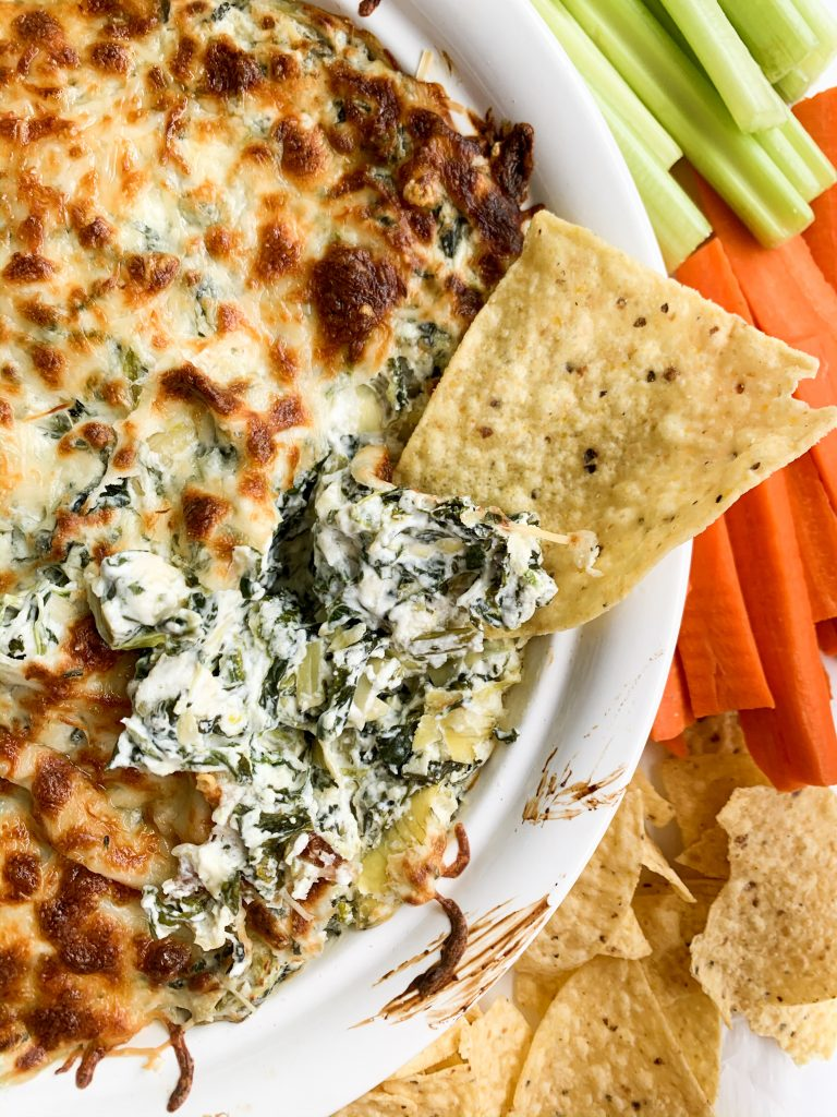 chip dipping into healthy spinach and artichoke dip
