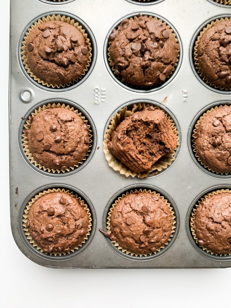 muffins in the pan still, one in the center with a bite taken out