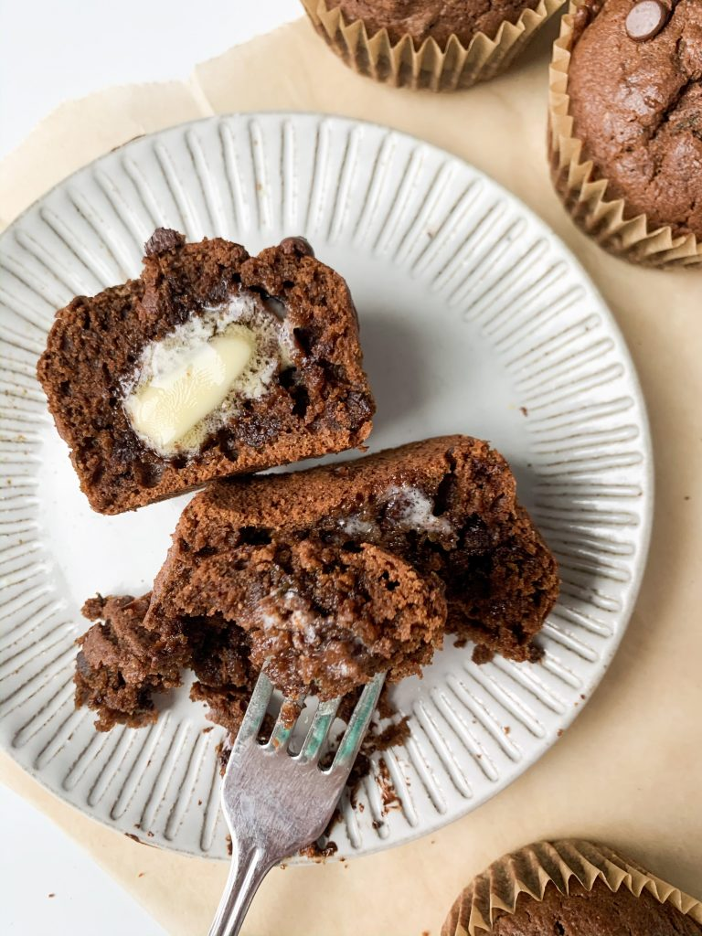 a plate with one chocolate zucchini muffin cut in half with butter on top