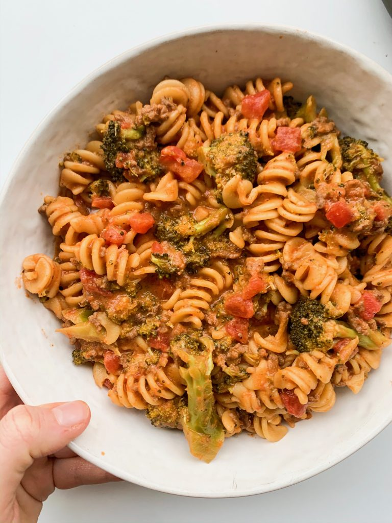 white bowl of ground beef, broccoli, and tomato sauce pasta