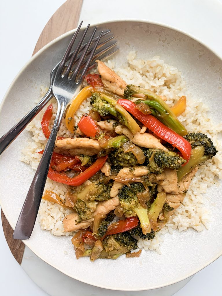 vegetables, chicken, and rice in a bowl with two forks