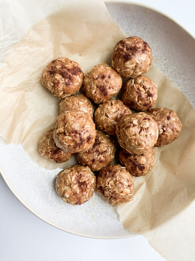 a bowl with parchment paper and peanut butter balls in it