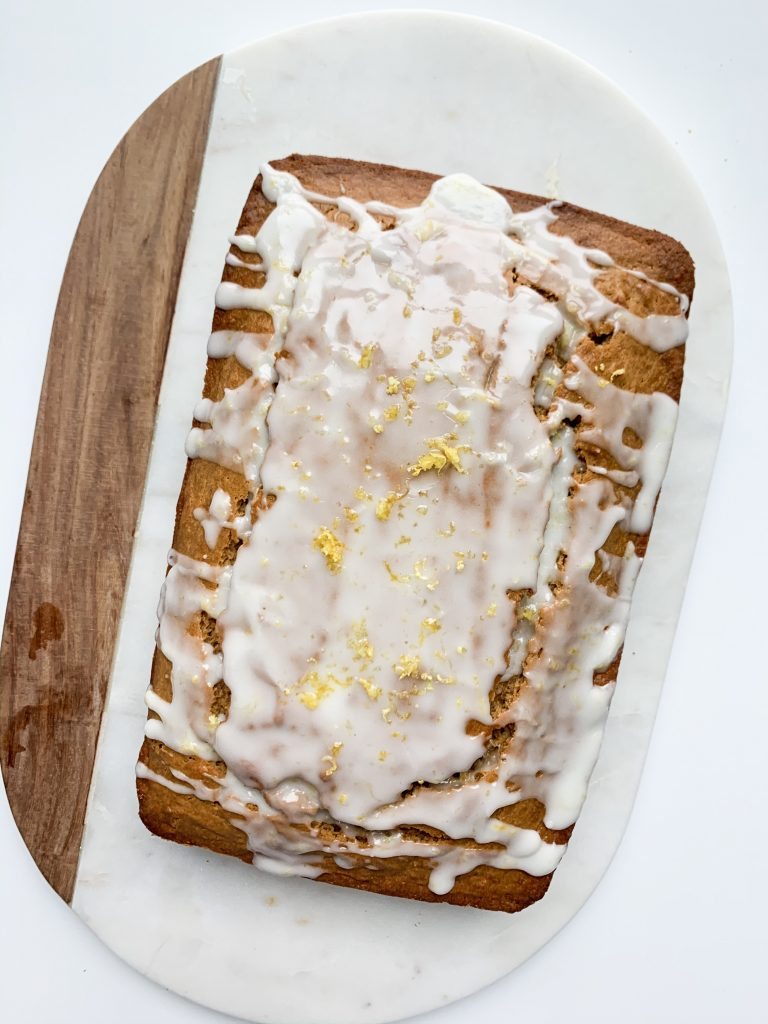 glazed lemon bread on a white and wooden board
