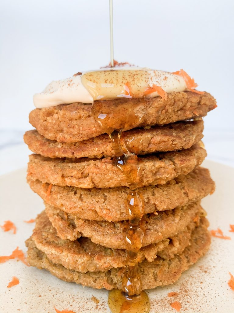 stack of healthy carrot cake pancakes with a maple syrup pour