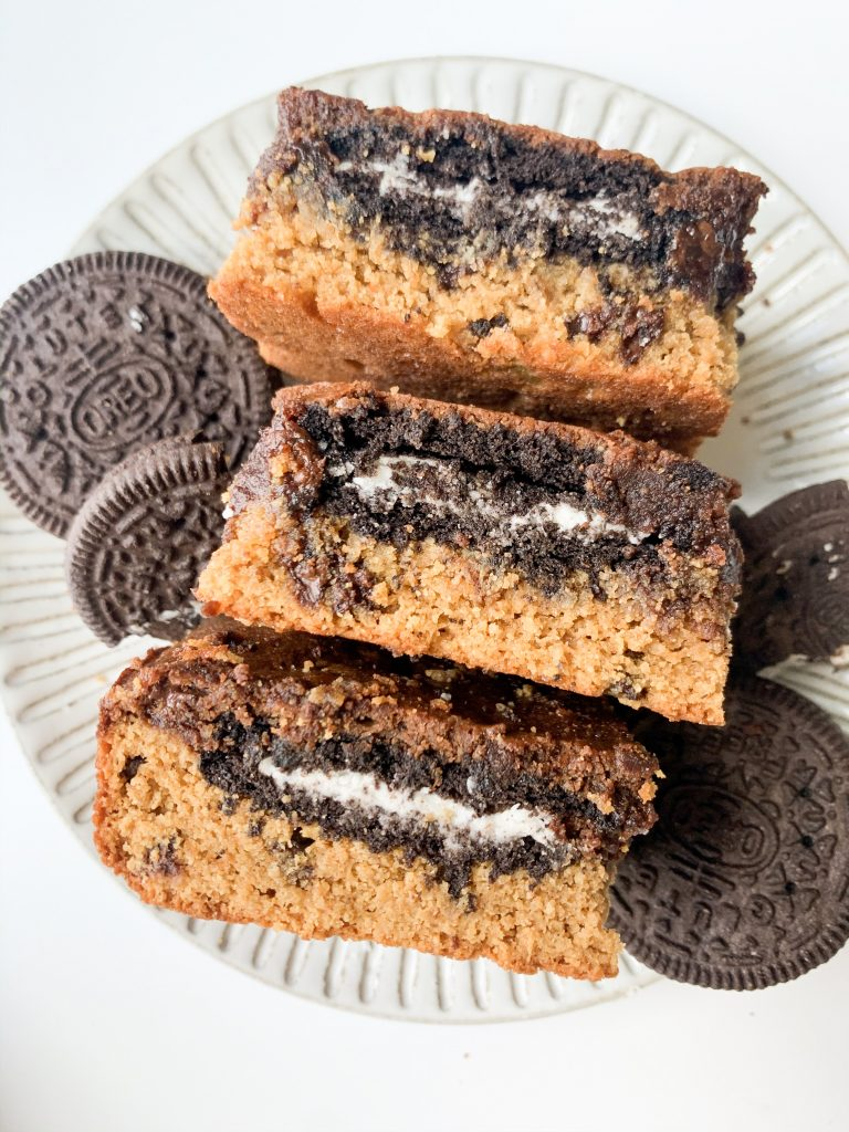 three gluten free slutty brownies on a plate with oreos