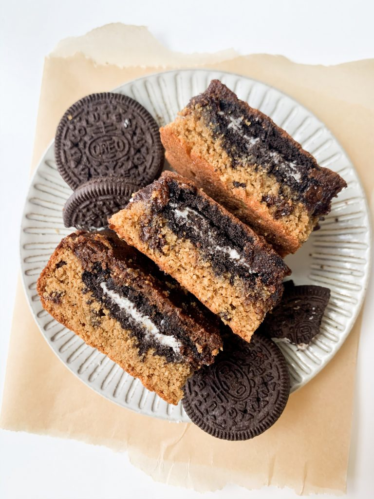 three oreo brownies on a gray plate on parchment paper