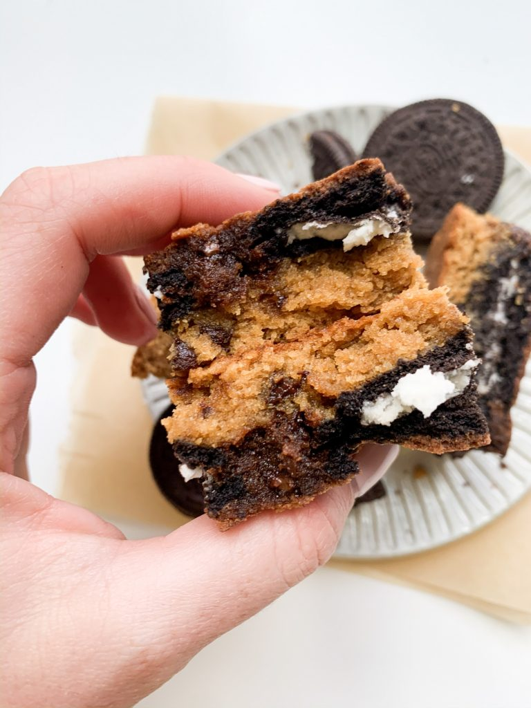 a hand holding an oreo cookie dough brownie