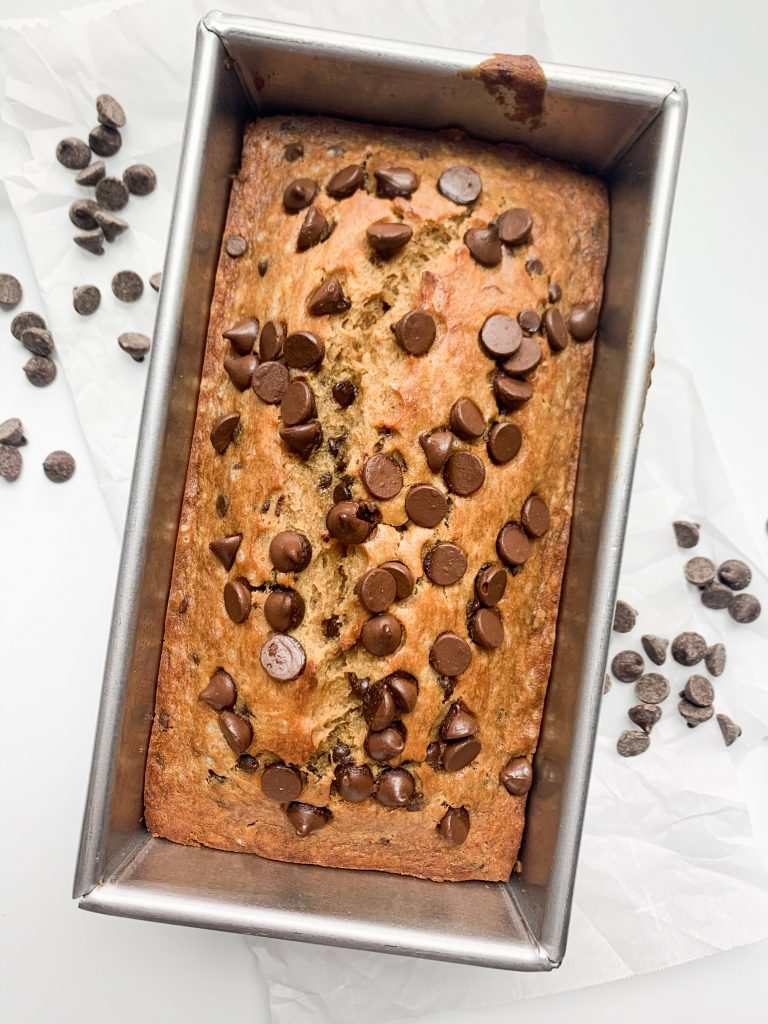 banana bread still in the loaf pan, on parchment paper, surrounded by chocolate chips