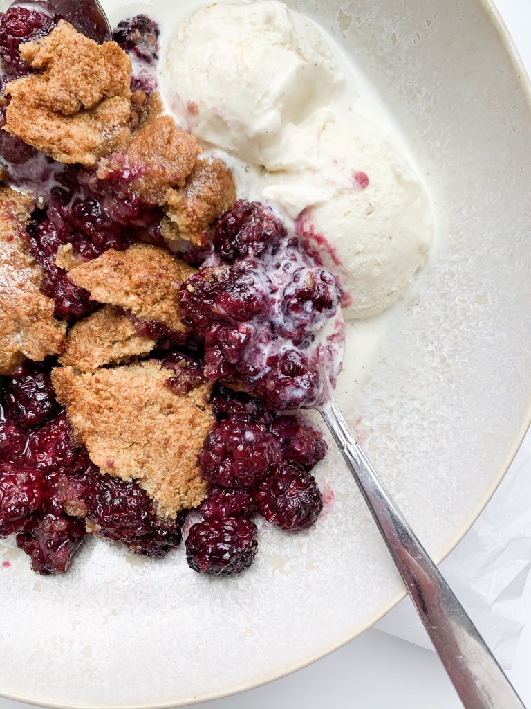 close up shot of a spoonful of blackberry cobbler and vanilla ice cream