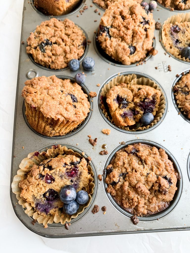blueberry crumb muffins in a muffin tin with extra blueberries