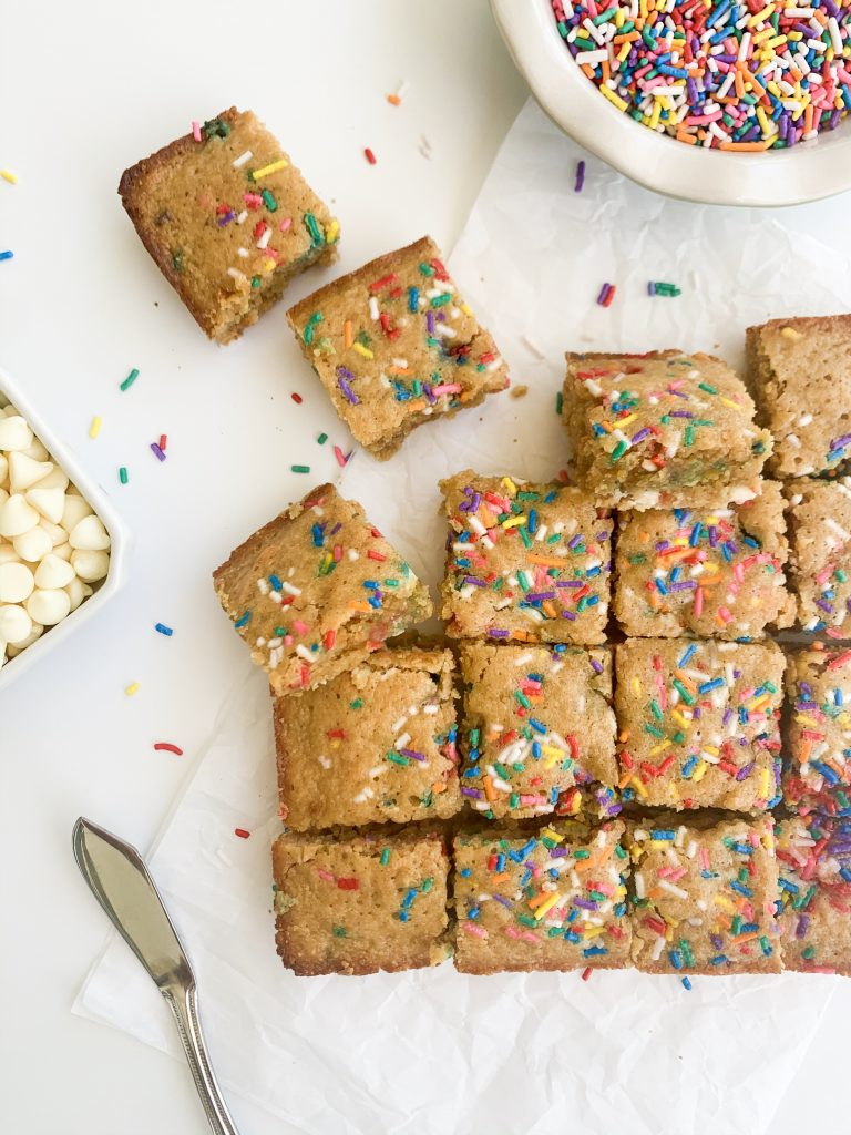 white background with blondies and a bowl of sprinkles and white chocolate chips