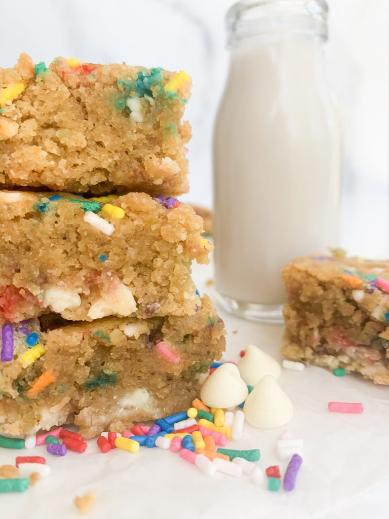 a closeup shot of a stack of blondies and a milk jug in the background