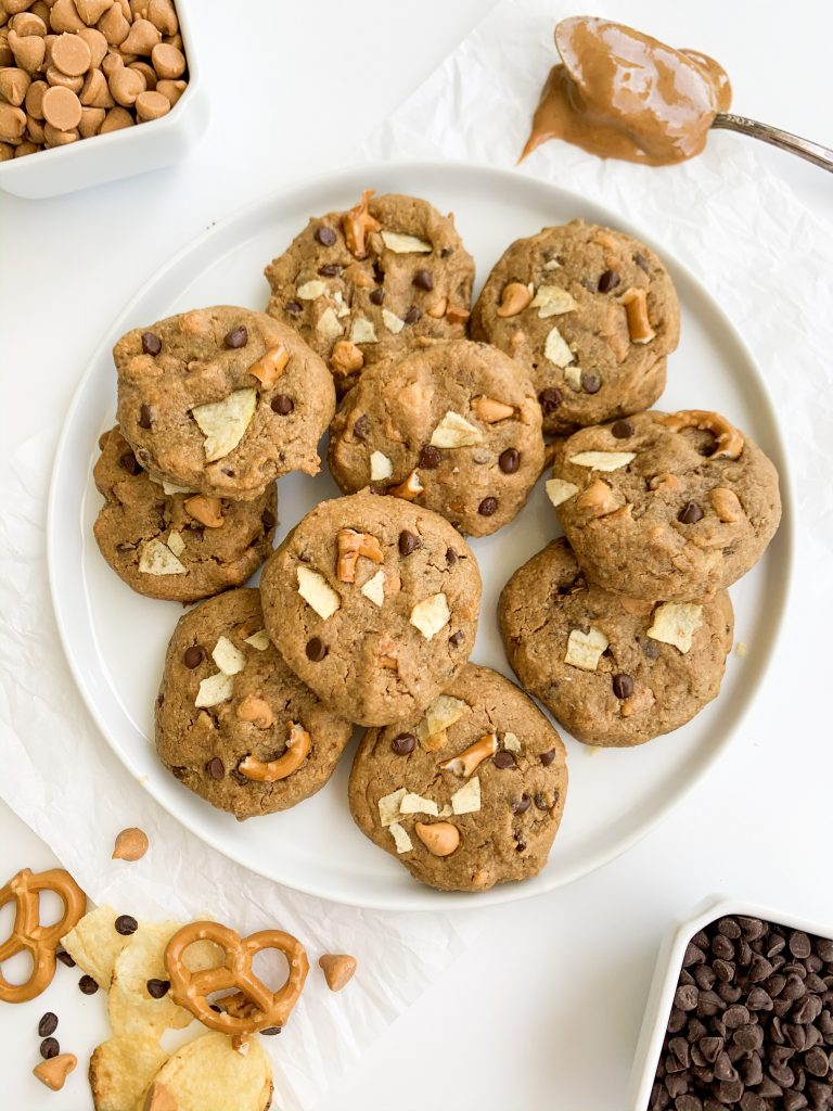 white plate of cookies surrounded by chocolate chips, pretzels, potato chips, and peanut butter