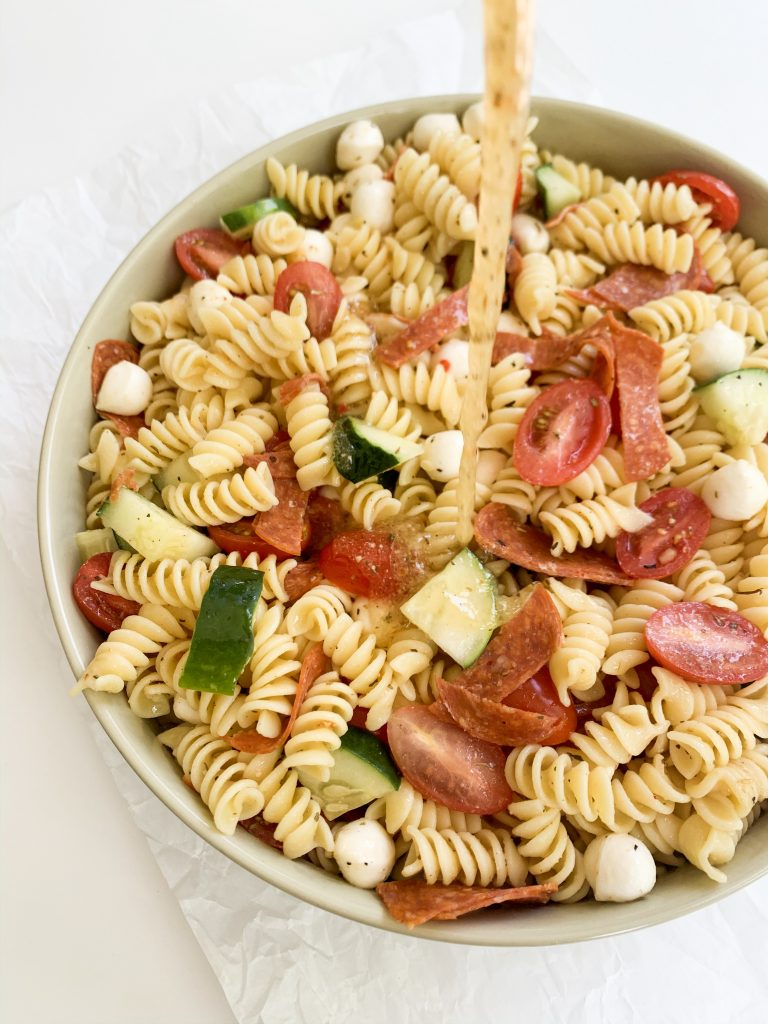 easy italian pasta salad with the dressing being poured on
