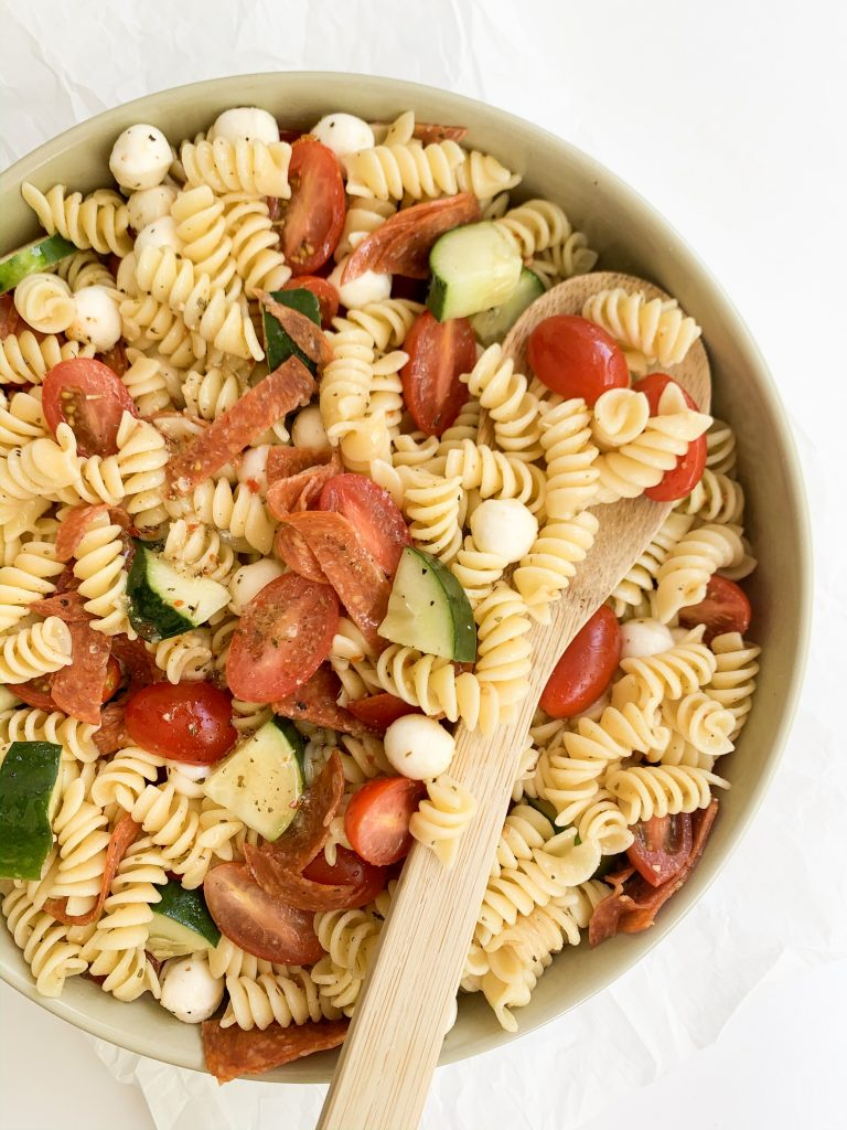 pasta salad in a large bowl with a wooden spoon