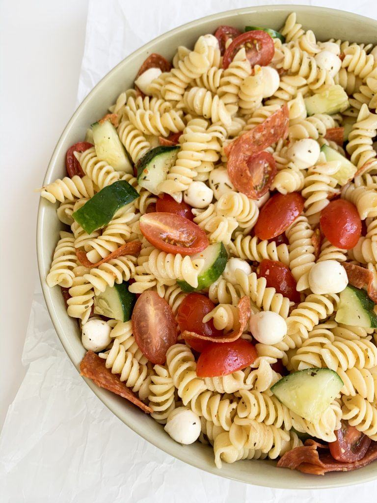 large bowl of pasta salad on a white background
