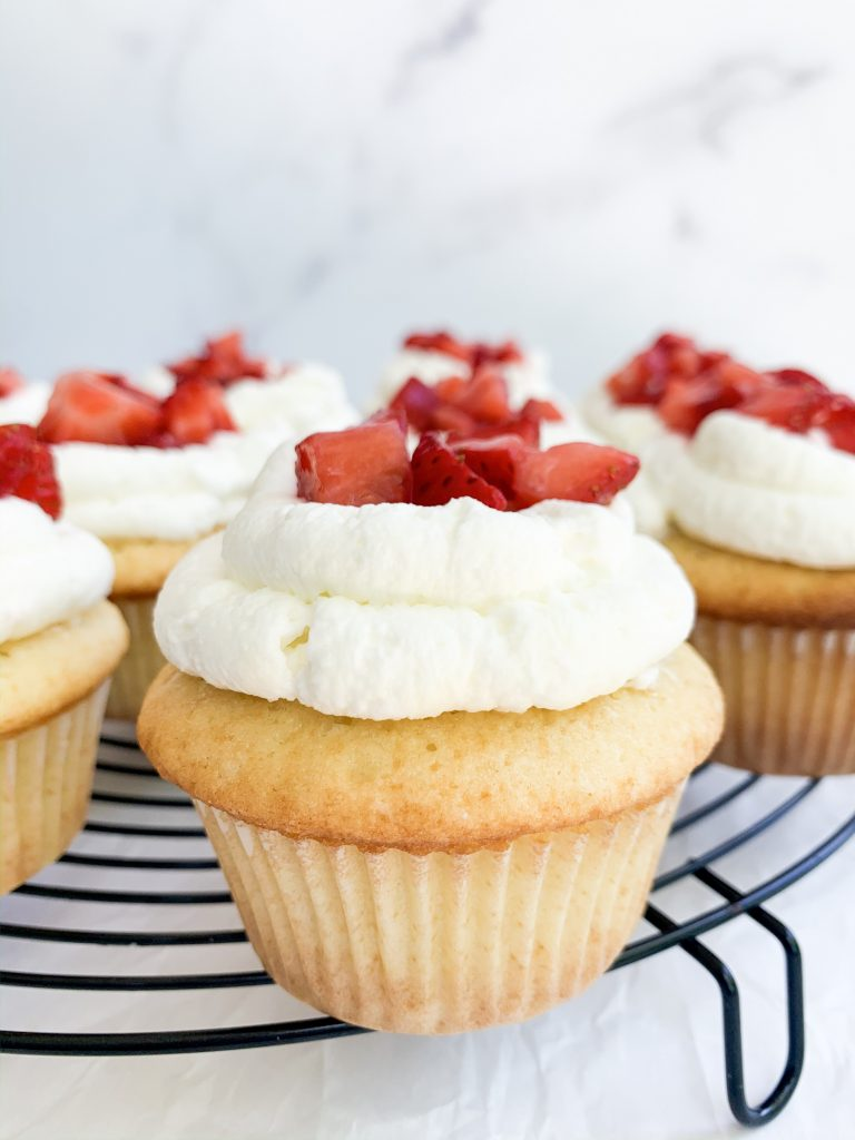 vanilla cupcake with whipped cream frosting and strawberries on a cooling rack