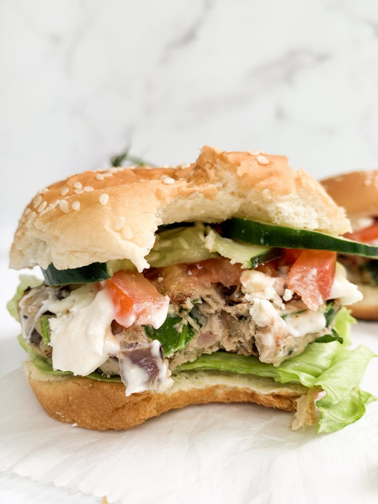 spinach & turkey burger on a bun with toppings and a bite taken out of it