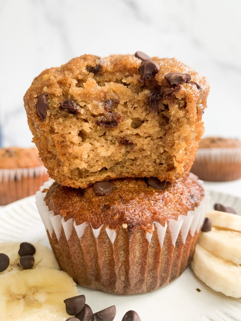 a stack of two banana muffins on a plate surrounded by banana slices and chocolate chips