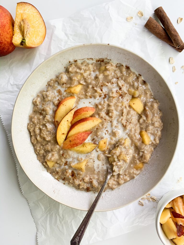 a bowl of peach oatmeal on a white background