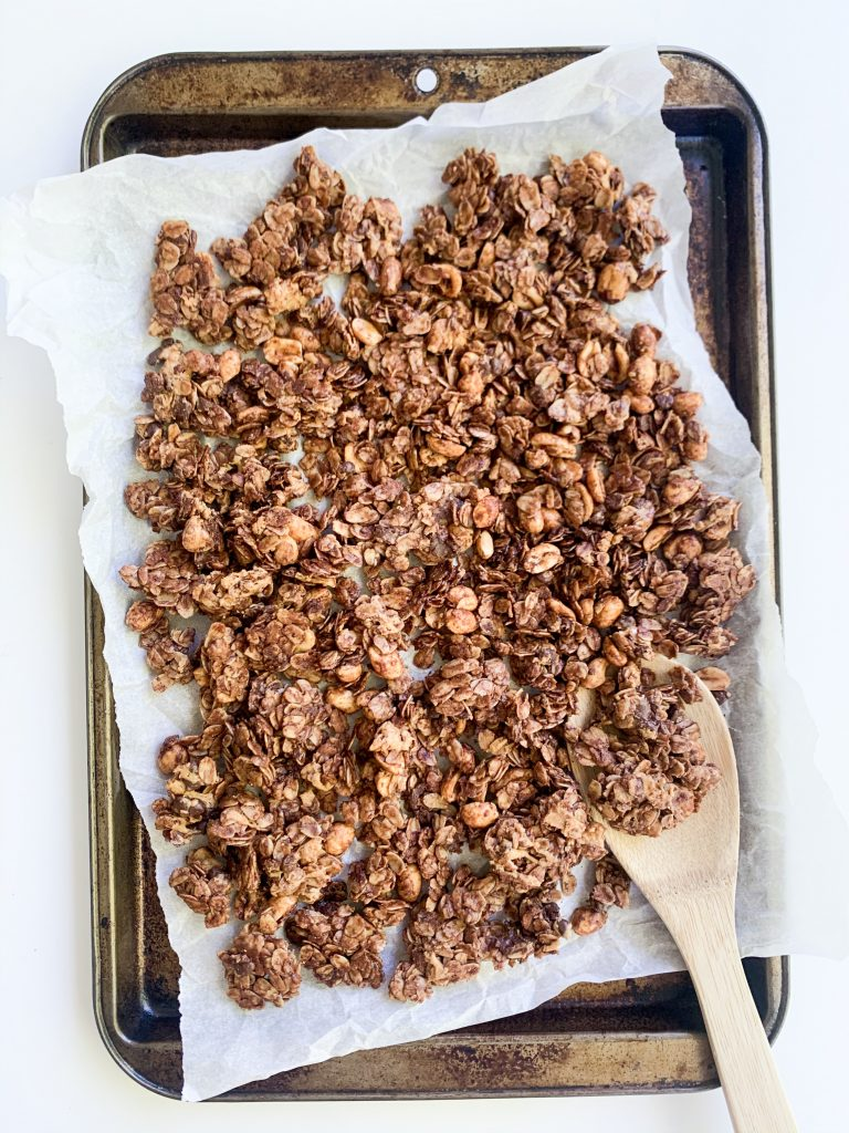 chocolate granola on  baking tray with a wooden spoon