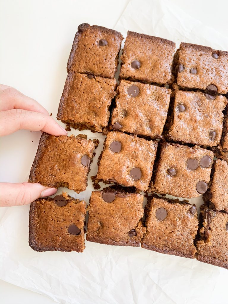 almond butter blondies on a white background with a hand taking one