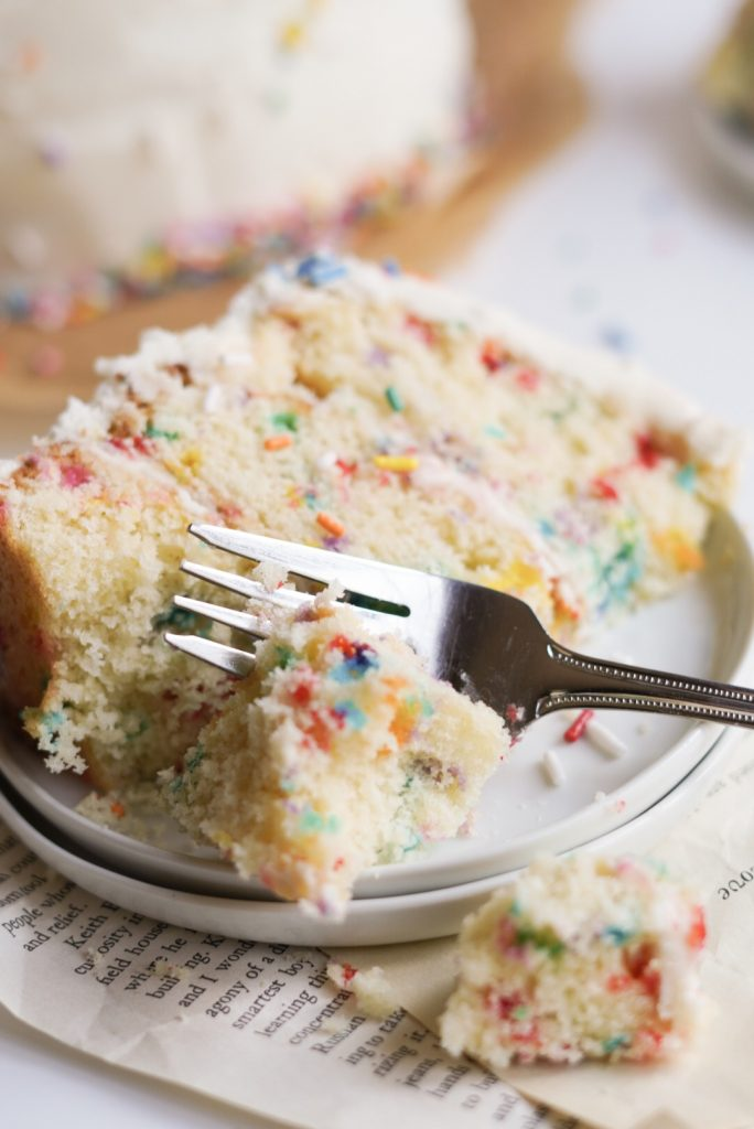 slice of funfetti cake on a plate with a fork taking a bite