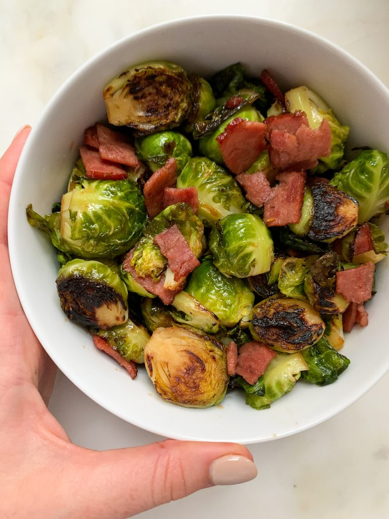 maple balsamic brussels sprouts with turkey bacon in a white bowl, with a hand holding the bowl